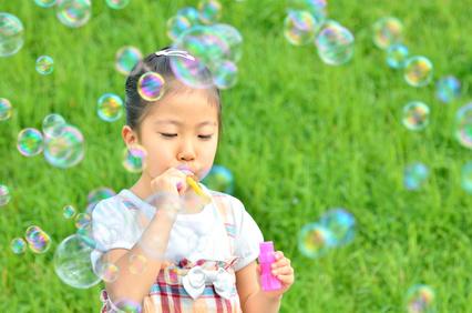 芝生広場でシャボン玉遊びをする女の子